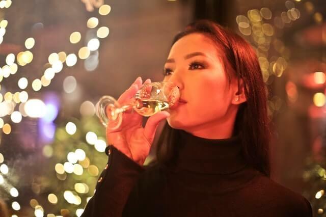 Fiatal hölgy pezsgőt iszik szilveszterkor